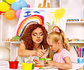 Child painting with mum.