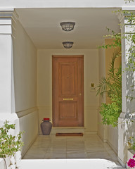 house entrance with solid wood door and flowerpot, Athens Greece