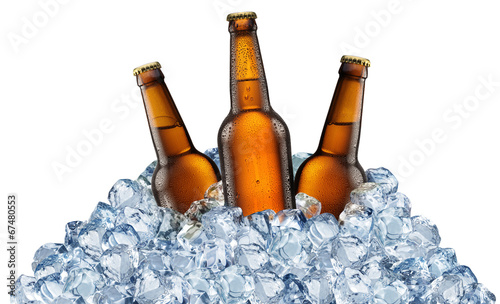 Three beer bottles getting cool in ice cubes. - 67480553