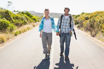 Attractive couple standing on the road holding hands smiling at