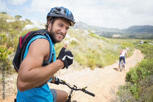 Fototapeta Fit couple cycling on mountain trail man smiling at camera