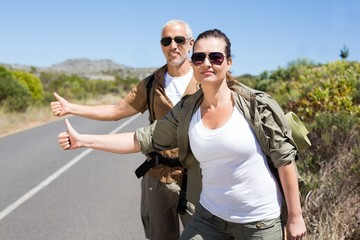 Hitch hiking couple standing on the side of the road with thumb