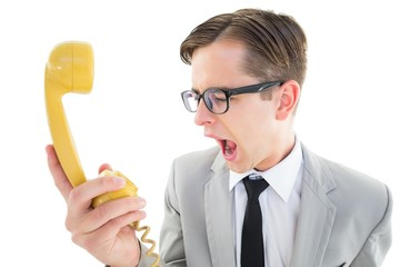 Geeky businessman shouting at retro phone