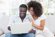 Attractive couple using laptop together on sofa to shop online