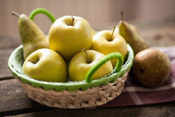 Fresh green apples and pears on a wooden table
