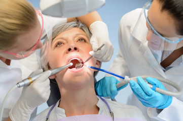 Senior woman patient dental check dentist team