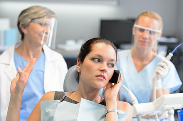 Impolite businesswoman on phone in dental office