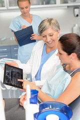 Patient at dental surgery dentist show xray tablet