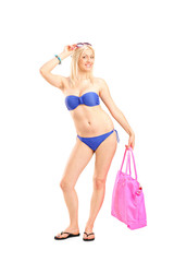 Full length portrait of a woman in bikini holding a bag