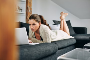 Young woman busy using a laptop at home