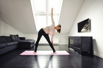 Fit woman doing stretching exercise at home