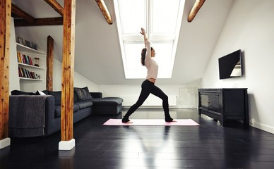 Healthy young lady going yoga workout at home