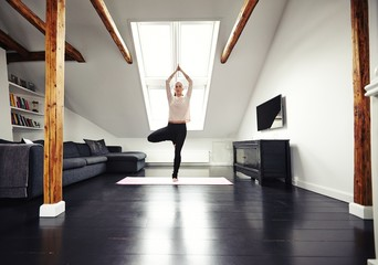 Young caucasian woman practicing yoga exercise at home