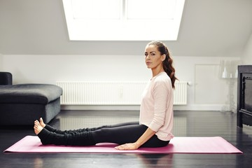 Fit young woman sitting on exercise mat - Indoors