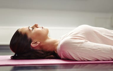 Woman lying on yoga mat relaxing her muscles