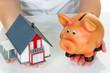 Frau mit Haus und Sparschwein