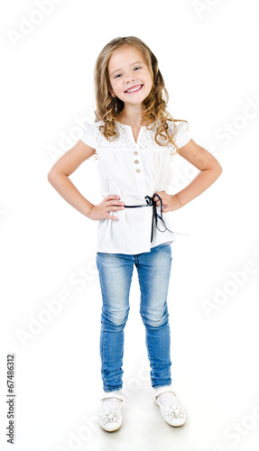 canvas print picture Cute smiling little girl in jeans isolated