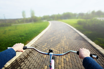 Woman riding a bicycle in park, handlebar view.
