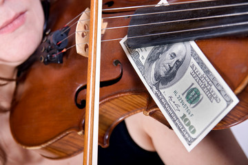 woman plays the viola with banknotes