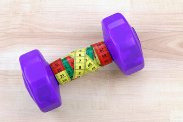A Purple dumbbell with measuring tape