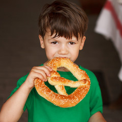 Little boy eat fresh pretzel