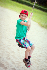 Little boy in red cap sit on swing rope