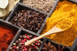 spices in box: pink black pepper, paprika powder, curry, bay lea