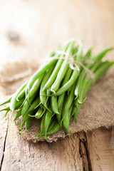 fresh green beans over wooden background