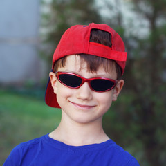 Little boy in red cap and sunglasses