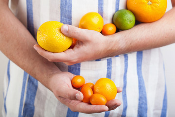 man hands holding various citrus fruits