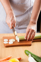 chef chopping leek in kitchen