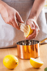 man squeezing lemon into a copper pot