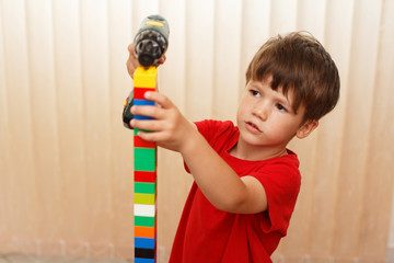 Little boy build tower from blocks