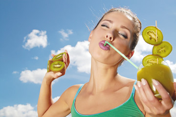 Happy young woman drinking kiwi juice over sky background