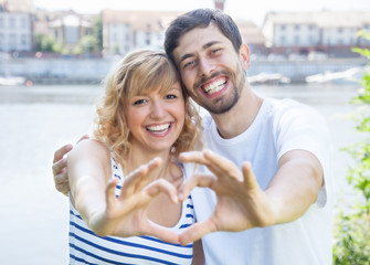 Couple in love outside showing heart with fingers