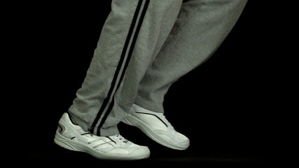 Legs in tracksuit running against black background