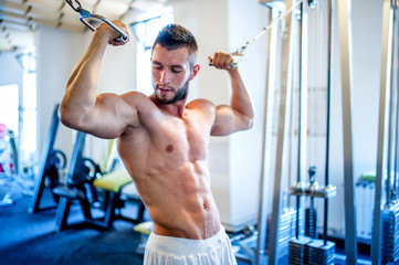 trainer, bodybuilder working out the biceps and the abs in gym