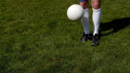 Football player controlling the ball on grass