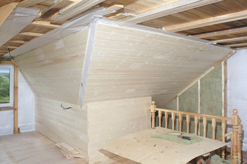 Attic under construction: mounting mineral cotton and deal board