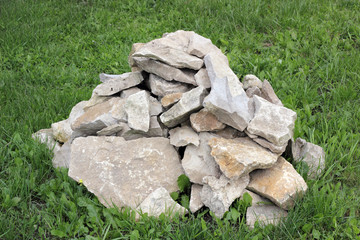 A pile of rough rocks on the green grass