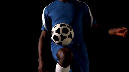 Football player in blue controlling the ball