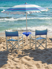 beach umbrella and chairs on the sea shore