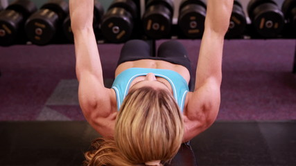 Super fit woman lying on bench lifting dumbbells at crossfit