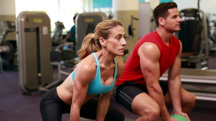 Two fit people squatting with medicine balls