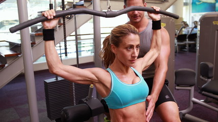Fit woman using the weights machine for her arms while trainer s