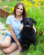 Teenager girl with black labrador retriever