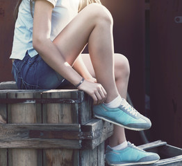 Blue sneakers on girl legs on the grunge background