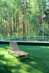 Wooden lounge chair on grass near  birchwood