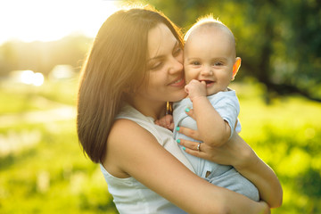 Happy mother holding a young son sunlight
