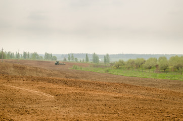 wide plowed field in rural image with tractor